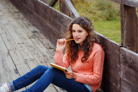 Young artist with sketch in note at autumn landscape photo