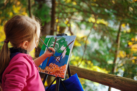 little painter at work in the mountains with palette Stock Photo