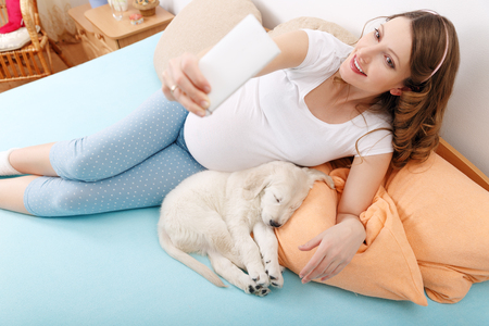 woman with phone: Pregnant woman making selfie shoot with her dog Stock Photo