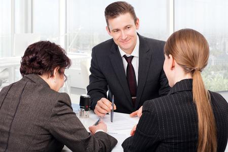 Agent of notaris tijdens documenten openbaar ondertekening met klanten