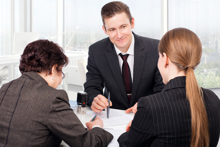 contrato de trabajo: Agente o notario durante la firma de documentos públicos con los clientes Foto de archivo