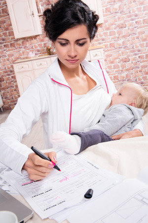 lactation: Young mother working while breastfeeding her baby Stock Photo