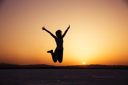 일몰 행복한 여자 점프의 실루엣 스톡 콘텐츠
