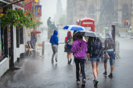 lluvia paraguas: Grupo de muchachas que date prisa en la lluvia con el paraguas en la ciudad