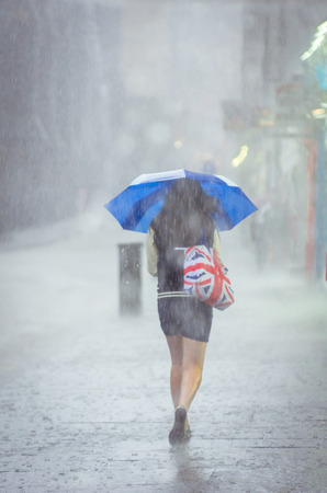 Girl walking in the rain with umbrella with bag with Britain flag print