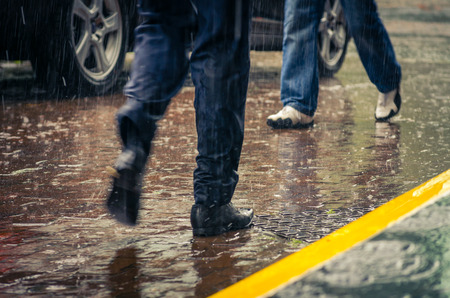 rainy: male feet stepping on wet from rain sidewalk in a city
