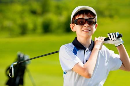 夏の日にゴルフ場で少年ゴルファーの肖像画
