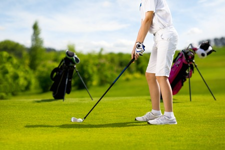 sports training: Legs of boy golfer with golf club at golf course at summer day