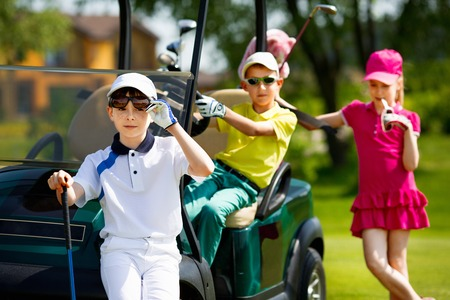 kinder: Children playing golf and taking part on kids competition in golf course at summer day