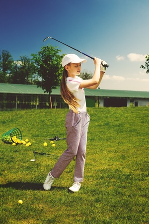practicing: Girl golf player practicing in golf school Stock Photo