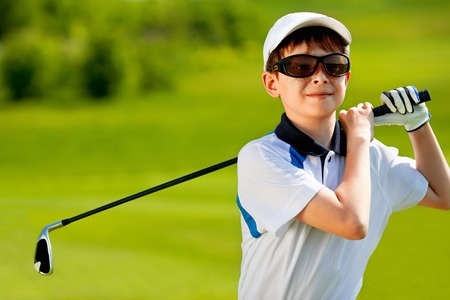 ni�os jugando: Retrato del golfista muchacho en campo de golf en d�a de verano