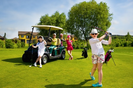 Children playing golf and taking part on kids competition in golf course at summer day