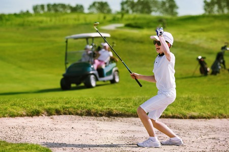 Boy playing golf and enjoing on the successful hit