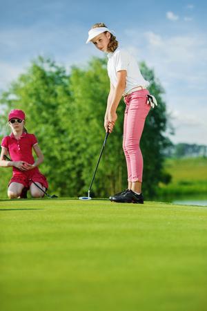 ゴルフで、グリーン上のパターで打つの女の子