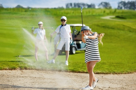 Girl playing golf and  hitting from bunker Stock Photo