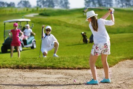 ゴルフ少女とバンカーから打つと 写真素材