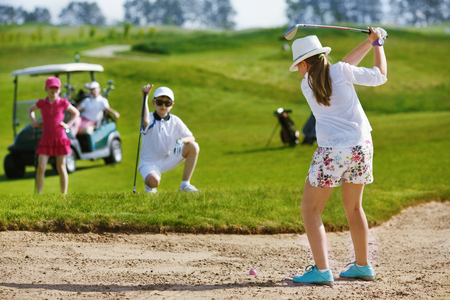 bunker: Girl playing golf and  and hitting from bunker Stock Photo