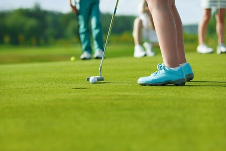 golfer: Legs of kids playing golf and hitting by putter on green