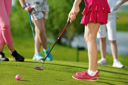 putter: Legs of kids playing golf and hitting by putter on green