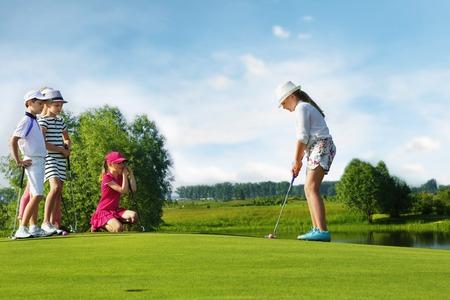 niños jugando en la escuela: Niños jugando al golf por putter en verde Foto de archivo