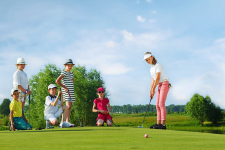 playing golf: Kids playing golf by putter on green
