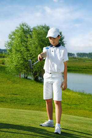 putter: Boy playing golf and hitting by putter on green