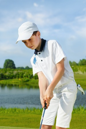 children sport: Boy playing golf and hitting by putter on green