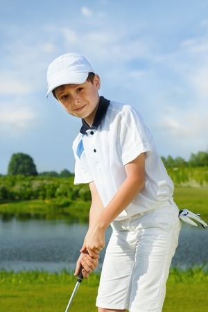 kids playing: Boy playing golf and hitting by putter on green