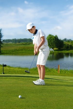 ni�os jugando: Boy playing golf and hitting by putter on green
