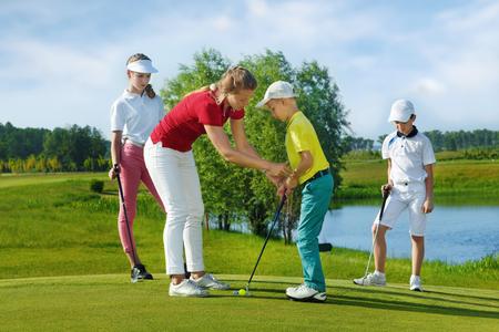 Los niños que practican con el entrenador en la escuela de golf en día de verano Foto de archivo - 47651152