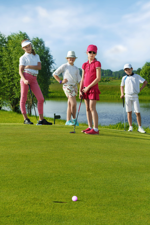 inaccurate: Kids playing golf by putter on green
