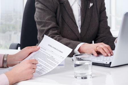 abogado: Manos de la firma del documento de la mujer en la oficina pública notarial