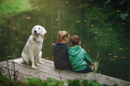 pesca: niña, niño y perro que juegan fuera - imitan la pesca en un lago