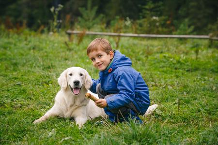 golden: Niño jugando en el césped del bosque con un golden retriever.