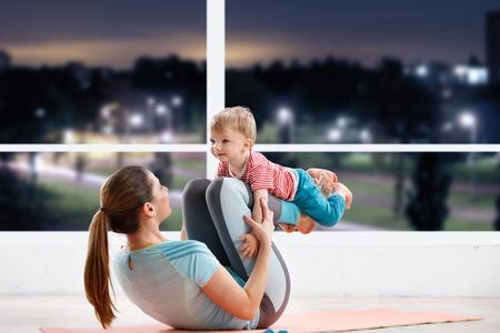 ejercicio aeróbico: entrenamiento madre en clase de gimnasia en la noche con su bebé Foto de archivo