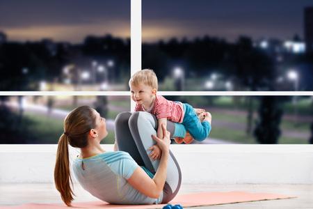 entrenamiento madre en clase de gimnasia en la noche con su bebé Foto de archivo