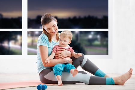 strenuous: Mother workout at fitness class in evening  with her baby