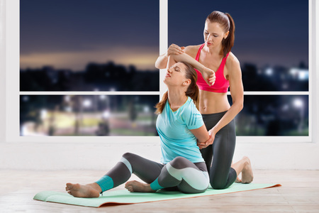 trainers: Instructor stretching a woman back in fitness class
