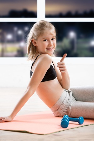 fitness, sport, yoga  - 10 years old  girl stretching  at fitness class in evening