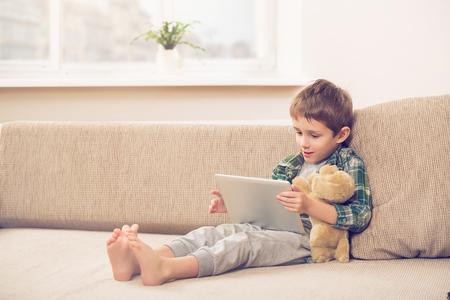 自宅のソファーにタブレット pc で遊ぶかわいい男の子