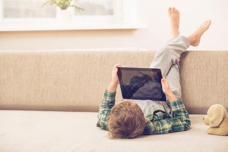solos: El niño pequeño lindo que juega con un Tablet PC en el sofá en casa