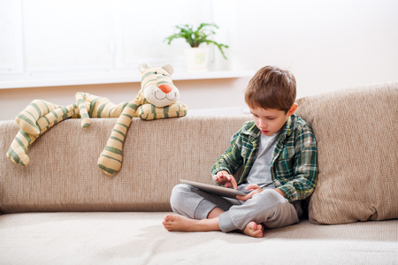 niños sentados: El niño pequeño lindo que juega con un Tablet PC en el sofá en casa