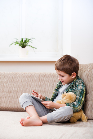 5 6 years: Cute little boy playing with a tablet pc on sofa at home