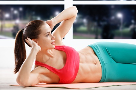 sexy abs: Portrait of athletic young woman workout at fitness class in evening Stock Photo