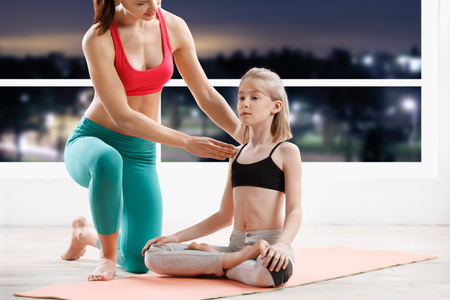 old girl: fitness, sport, yoga  - 10 years old  girl stretching  with personal trainer at fitness class in evening