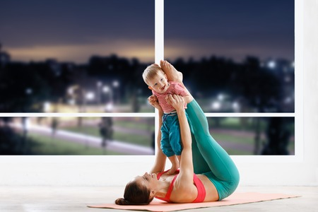 evening class: athetic woman working out with little baby at fitness class in evening Stock Photo