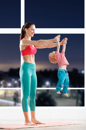 evening out: athetic woman working out with little baby at fitness class in evening Stock Photo