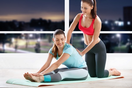 fitness gym: young woman workout at fitness class with trainer in evening
