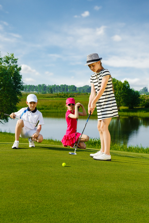 putter: Kids playing golf by putter on green