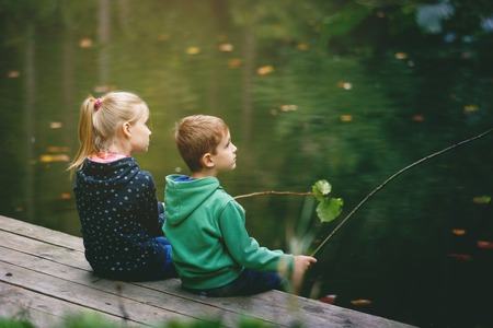 imitate: Brother and sister playing outside - imitate fishing at a lake
